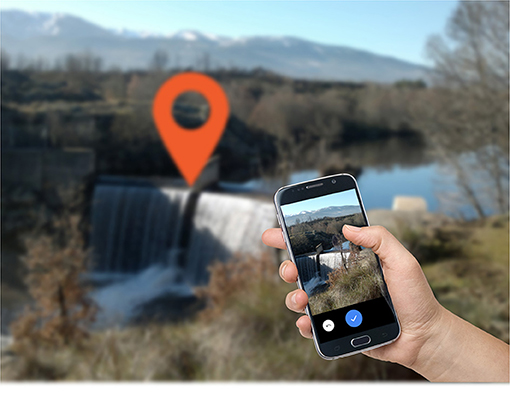 Figure 3 - A community member taking a photo and geotagging a dam and reservoir with the Adaptive Management of Barriers in European Rivers (AMBER) smartphone app (Image courtesy of AMBER Project).