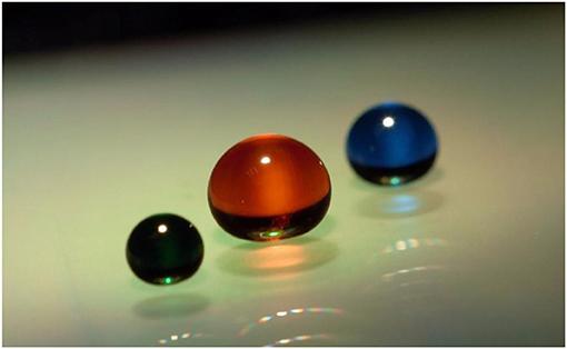 איור 3 - שלוש טיפות מונחות על משטח סופר-הידרופובי (דוחה מים).